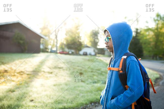 Boy wearing blue hoodie waiting at bus stop
