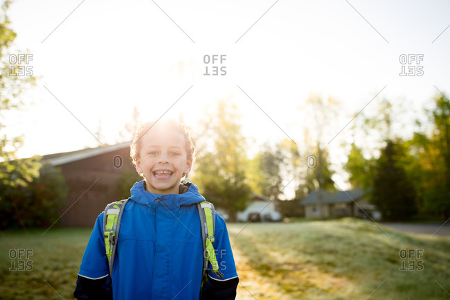 Curly haired boy waiting at bus stop