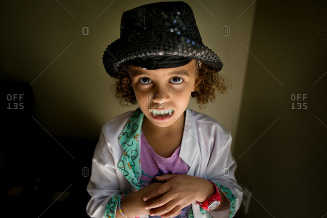 Little girl playing dress up in a hat, doctor's coat and fangs