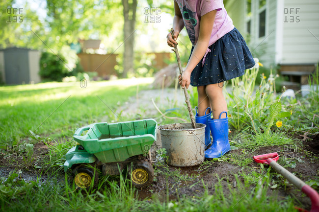 Girl stirring bucket of dirt with a stick