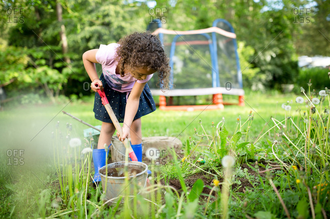 Girl digging in dirt with a shovel
