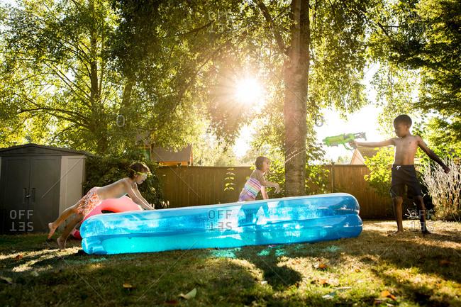 Kids playing in backyard swimming pool