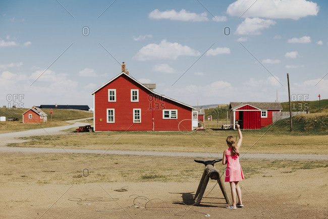 Girl twirling a lasso in the air on a farm