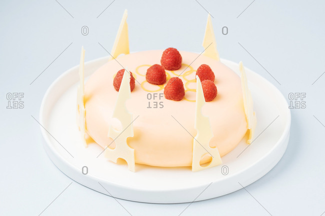 Pink cake with sugar icing, cheese wedges and raspberries
