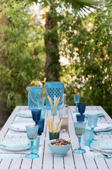 Set outdoor table with plates, wine glasses, olives, and breadsticks