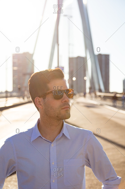 A handsome man stands on a bridge at golden hour
