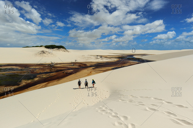 A group of tourists crossing sand dunes and lagoons in Lencois Maranhenses National Park