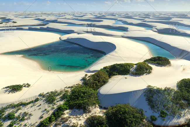 Aerial view of sand dunes, lagoons, and vegetation in Lencois Maranhenses National Park