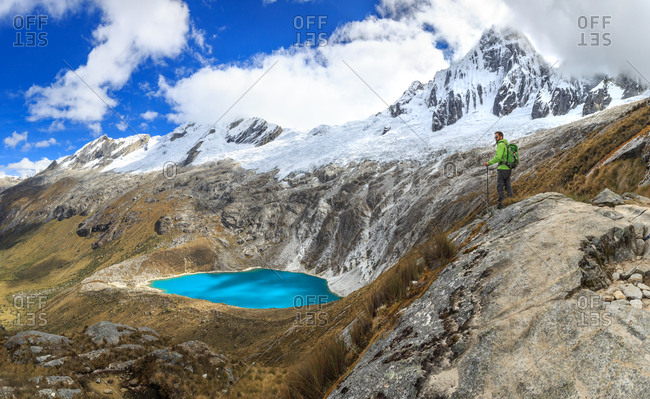 A mountaineer contemplates the view of a lake and snowcapped mountains at Cordillera Blanca