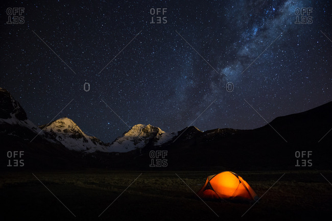 A campsite and the starry sky with snowcapped mountains in the background
