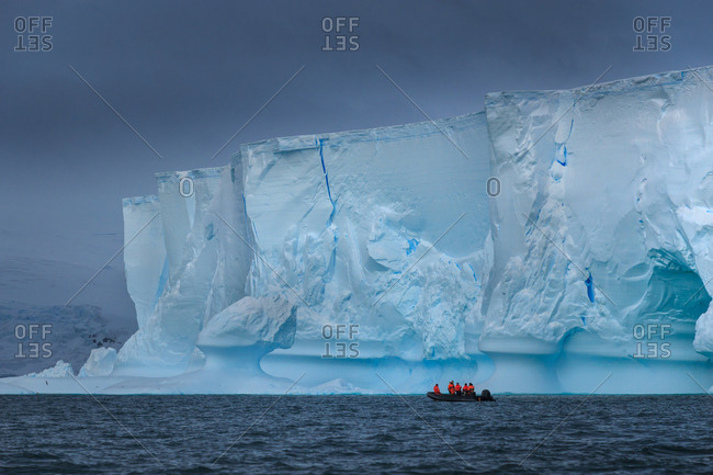 Boat with researchers in front of an iceberg