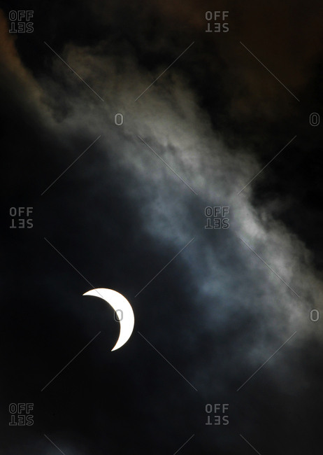 Storm clouds move in front of the eclipse of the sun