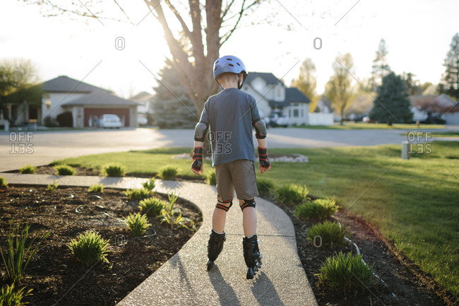 Boy riding inline skates in front yard