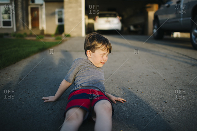 Boy crying lying in driveway