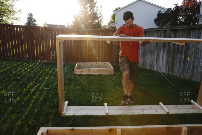 Man building wood box in yard