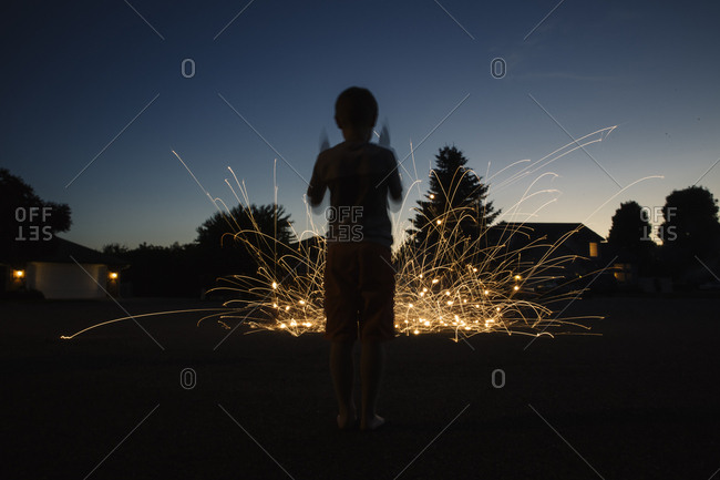 Boy in silhouette with sparklers