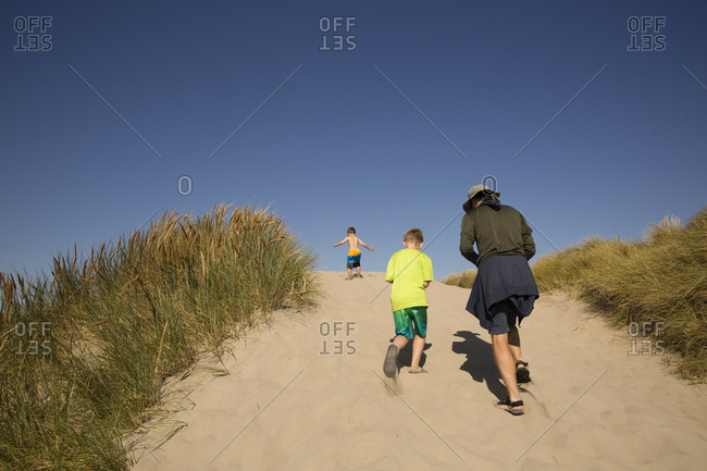 Two boys and adult on sand dunes