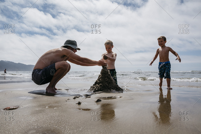 Boys and man playing with wet sand