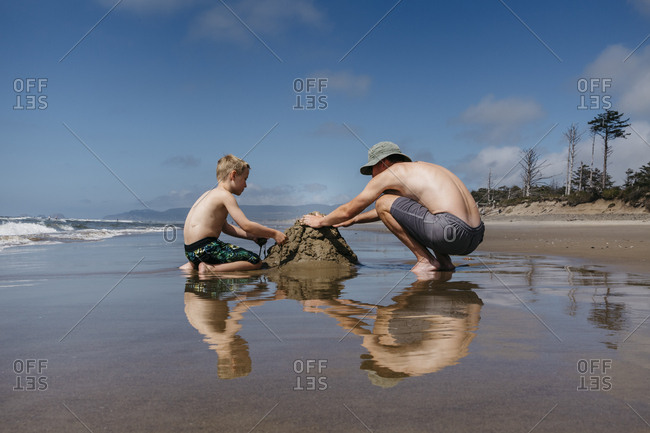 Boy and man playing with sand
