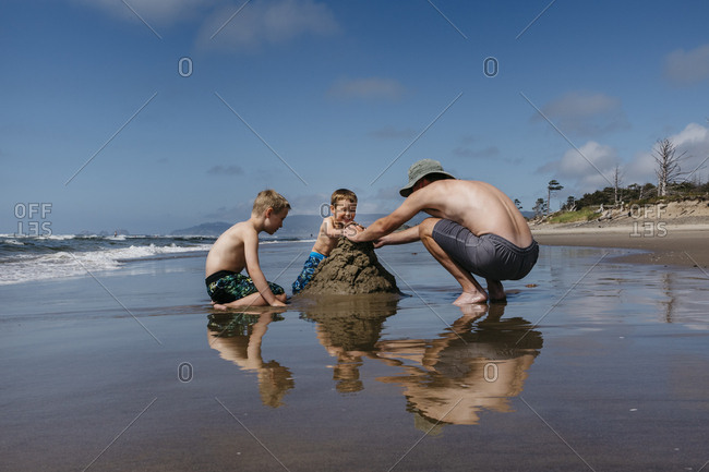 Boys and man playing with sand