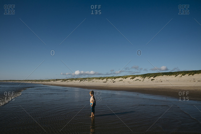 Boy standing still in ocean