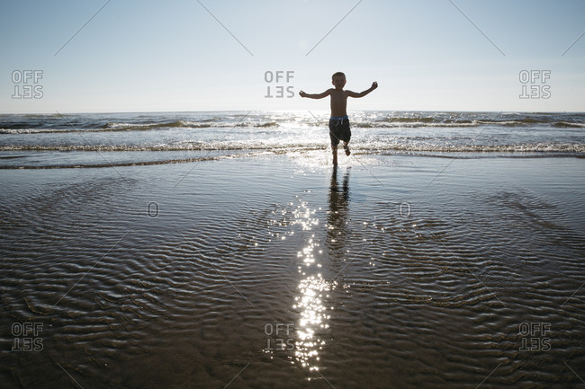Boy in sunlight running in ocean