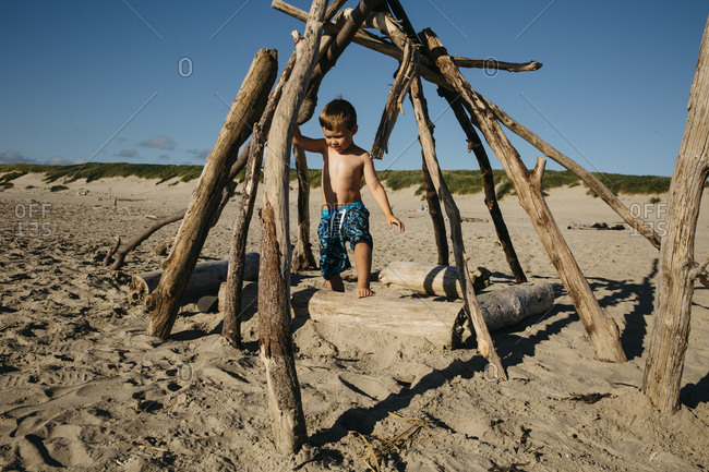 Boy exploring beach stick structure