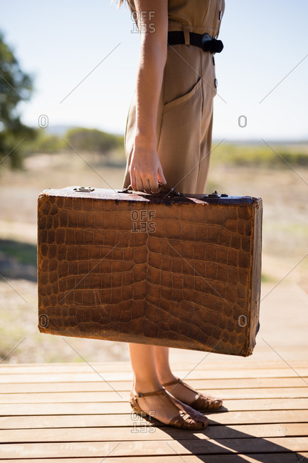Woman with suitcase standing on deck on a sunny day during safari vacation