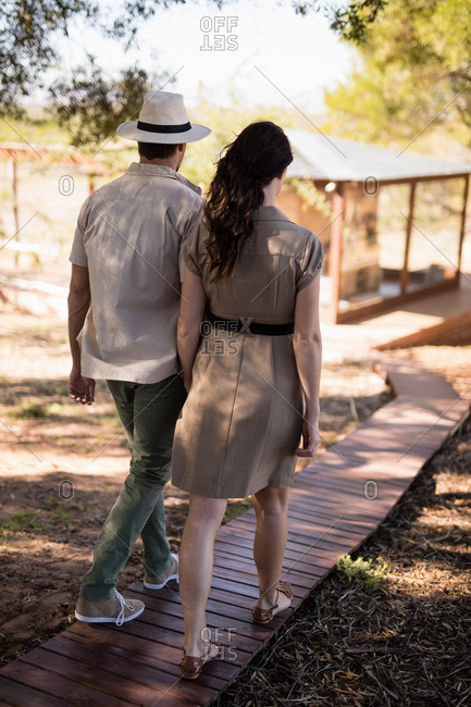 Rear view of couple walking on wooden deck during safari vacation