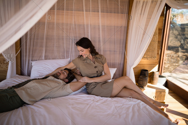 Couple relaxing on canopy bed in cottage during safari vacation