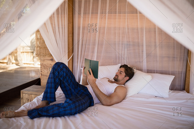 Man reading novel on canopy bed during safari vacation