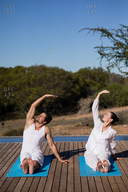 Couple performing yoga at safari vacation on a sunny day