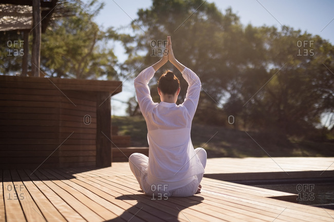 Woman performing yoga on wooden plank on a sunny day