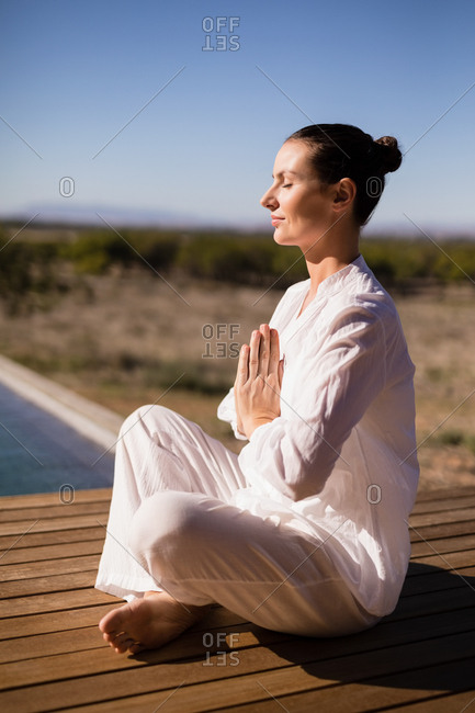 Woman performing yoga near poolside on a sunny day