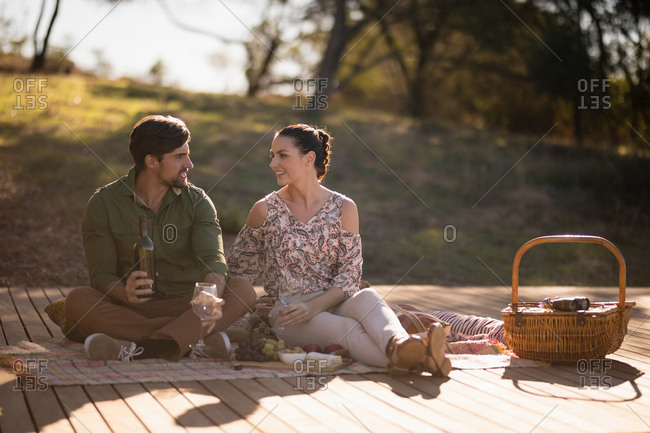 Couple having drinks together on wooden plank during safari vacation