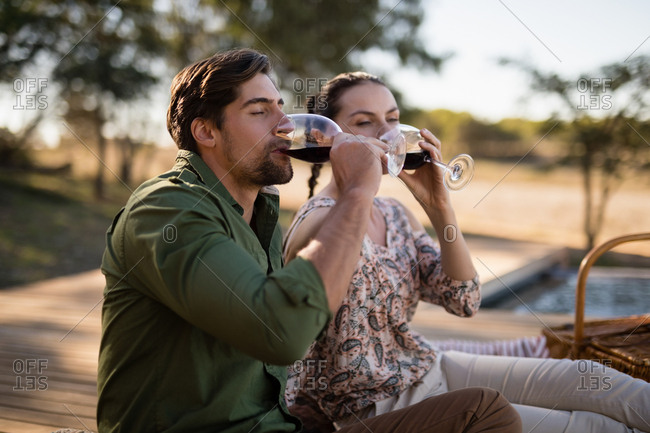 Romantic couple drinking red wine during safari vacation
