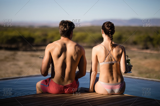 Rear view of couple relaxing in pool