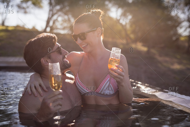 Happy couple having champagne in pool