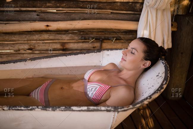 Woman sleeping in bathtub during safari vacation