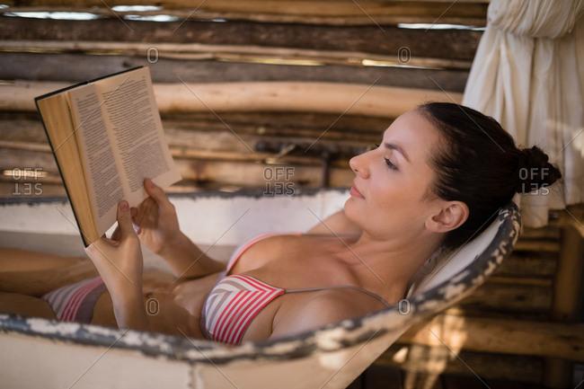 Woman reading a novel in bathtub during safari vacation