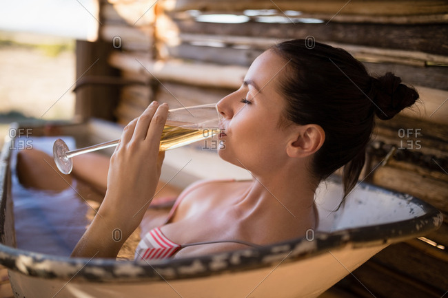 Woman having champagne in bathtub during safari vacation