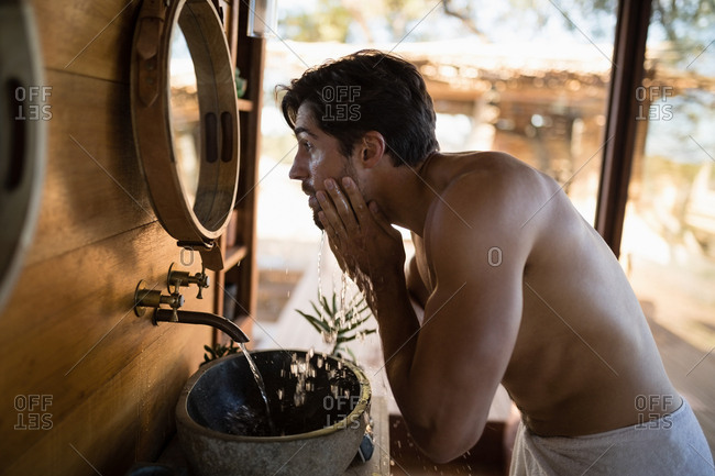 Man washing face from water in cottage during safari vacation