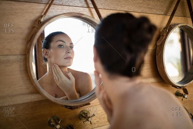 Woman looking at mirror in cottage during safari vacation