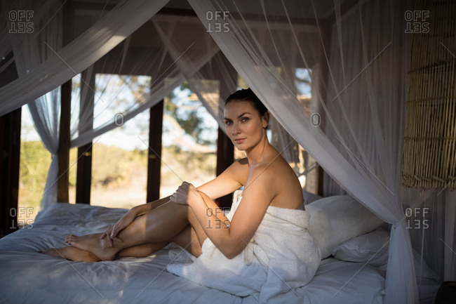 Portrait of woman in towel sitting on a canopy bed in cottage