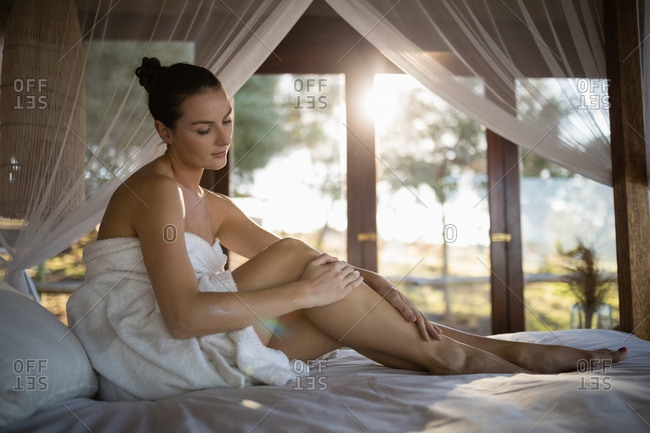 Woman applying lotion while sitting on canopy bed in cottage