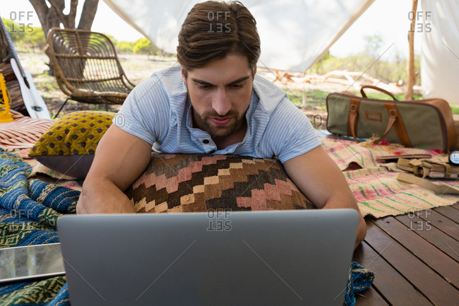 Relaxed young man using laptop while lying down in tent