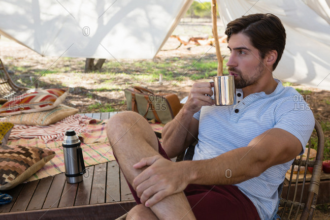 Thoughtful young man drinking coffee in tent