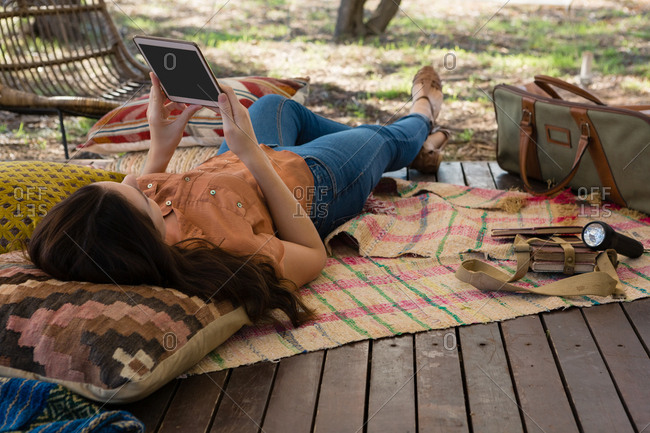 Woman using digital tablet while lying down in tent