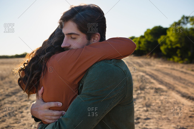 Young couple embracing against sky on field