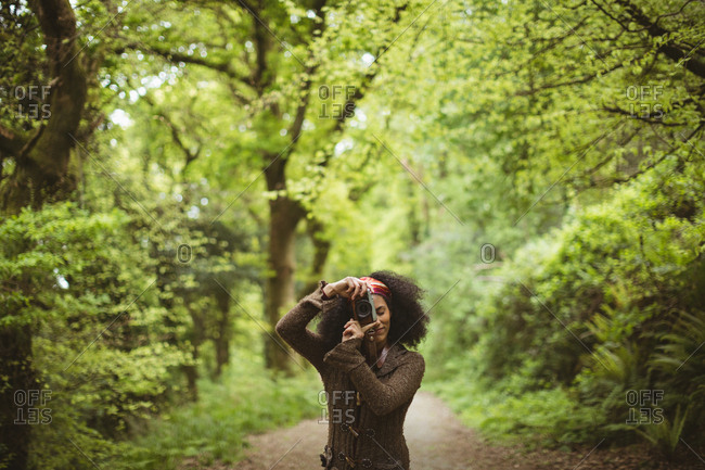 Woman photographing from camera while standing at forest